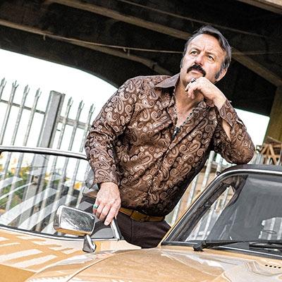 Comedian Mike Bubbins leans on a vintage car