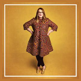 A full-body promotional shot of Sarah - she stands, wearing a colourful dress, with her hands on her hips. The background is a deep mustard colour.