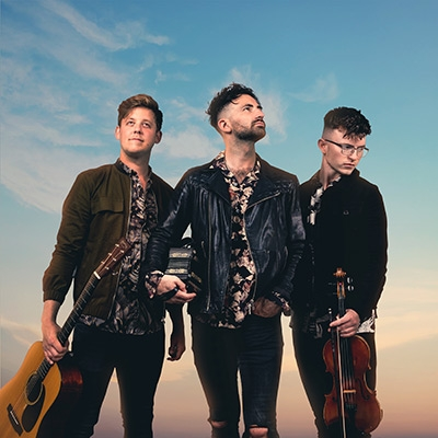 The three members of Talisk hold their their instruments against a blue sky