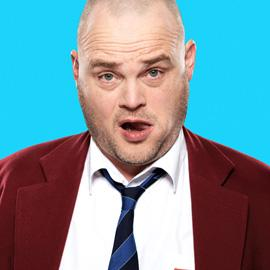 A close-up image of Al Murray - who is sticking his tongue in his cheek - against a bright blue background.