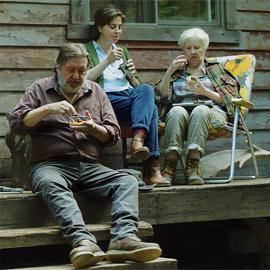 three people sitting outside on a porch