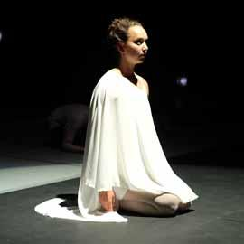 A kneeling dancer performer, dressed in white on a dark stage.