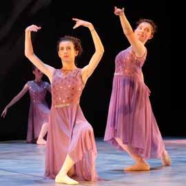 Two young ballet dancers on stage, in long pink dresses.