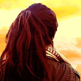 A figure long hair, their back to the camera, looks straight ahead at a yellow sky.