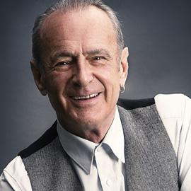 Francis Rossi smiles at the camera. He's wearing a white shirt and a grey waistcoat.