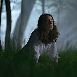 A girl in a white shirt kneels in a wood
