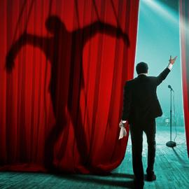 "Man about to go out on stage seen from behind with his arm held up in a greeting. His ""shadow"" shows a man with his body representing the letter M or possibly flying?"
