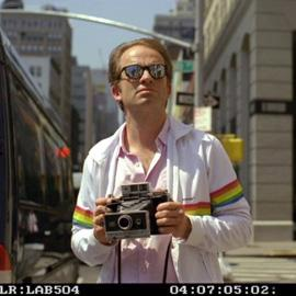 Man holding a Polaroid camera in a street.