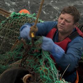 Fisherman on boat preparing a net.