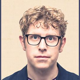 A close-up of Josh, who has curly blond hair and black-rimmed glasses.