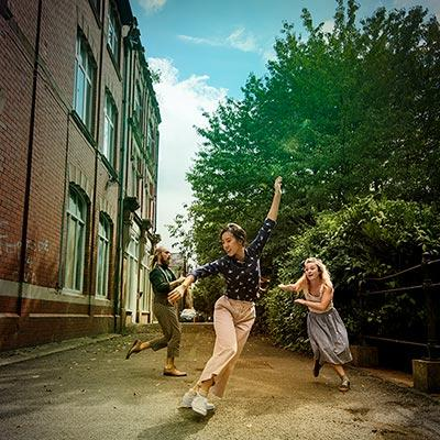 Poster for Open Air Performance from National Dance Company Wales. Three people dance joyfully