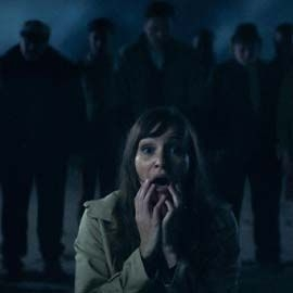 Close up of a girl with her hands to her mouth, in the background there are shadowed figures