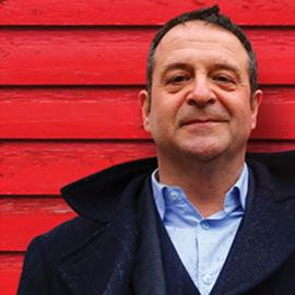 A head-and-shoulders image of Mark Thomas, behind him a red wall made of wood (presumably a shed!).