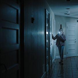 a woman holding a torch walks down a dark corridor