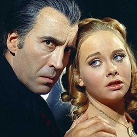 Christopher Lee as Dracula holding the shoulder of a young girl