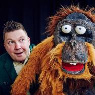 Jeremiah Johnson grins at a large Orangutan puppet