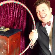 Jeremiah Johnson holds a hula-hoop round a large pretend snail on a plinth