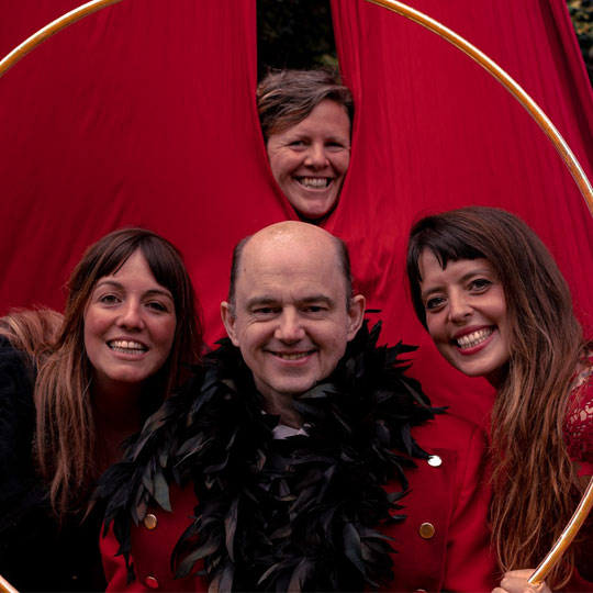 Photograph of the cast of Bring Me Sunshine all framed by a hula-hoop against a red curtain