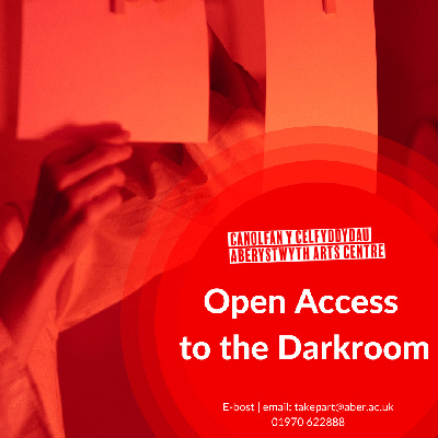 A person hangs photographs to develop in a darkroom. Text reads Open access to the darkroom