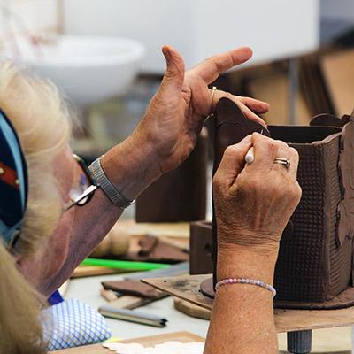 A woman sculpts a clay shape