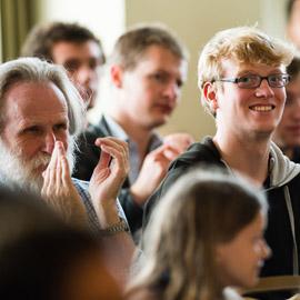 An audience of people, some blurry, and at centre a young man wearing glasses smiles at the camera.   Cynulleidfa o bobl, rhai'n aneglur, ac yn eu canol dyn ifanc sy'n gwisgo sbectol ac yn gwenu i'r camera.