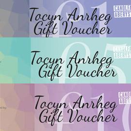 A colourful image featuring the gift voucher designs in purple, green and pink.   Delwedd lliwgar sy'n dangos dyluniadau y tocynnau anrheg, mewn lliwiau glas, gwyrdd a phiws.