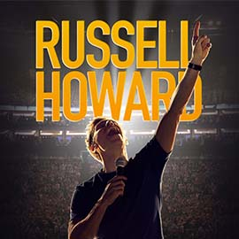 A stylised imaged of Russel Howard, one arm raised in the sky, another holding a microphone. An indistinct crowd is behind him, as well as large, yellow lettering spelling his name.