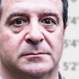 A close-up of Mark Thomas's face with a neutral expression | Llun agos o wyneb Mark Thomas, gyda edrychiad niwtral.