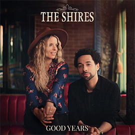 A promotional image of The Shires, a duo, who sit in a rustic looking room.