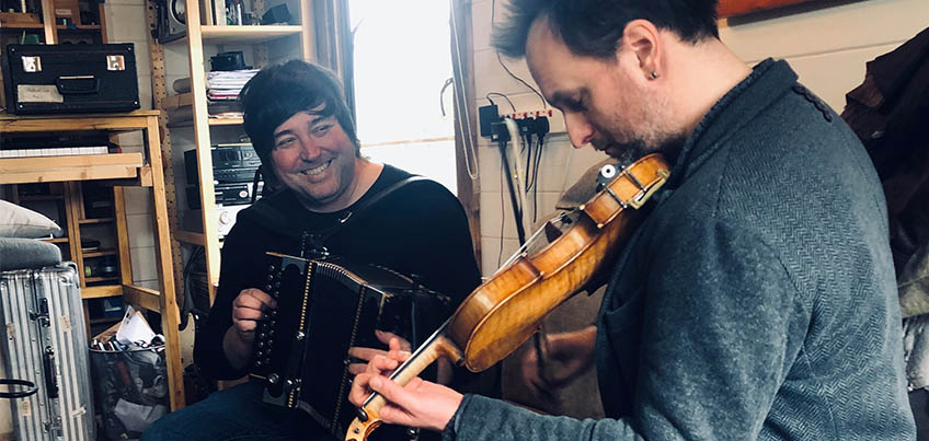 Two men sat on a sofa playing a violin and an accordion